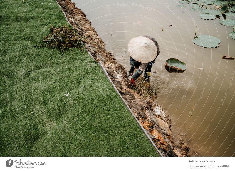 Arbeiter im kegelförmigen Hut Unkrautjäten Boden in Flussnähe kultivieren Person Landwirt Hacke Vietnam Asien Wasser dreckig Strohhut Garten Werkzeug