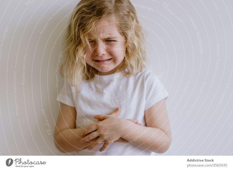 Kleines weinendes Mädchen im Studio unanständig wenig Kind verschränkte Arme jammern lässig traurig Stirnrunzeln enttäuschen Kindheit Gesichtsausdruck