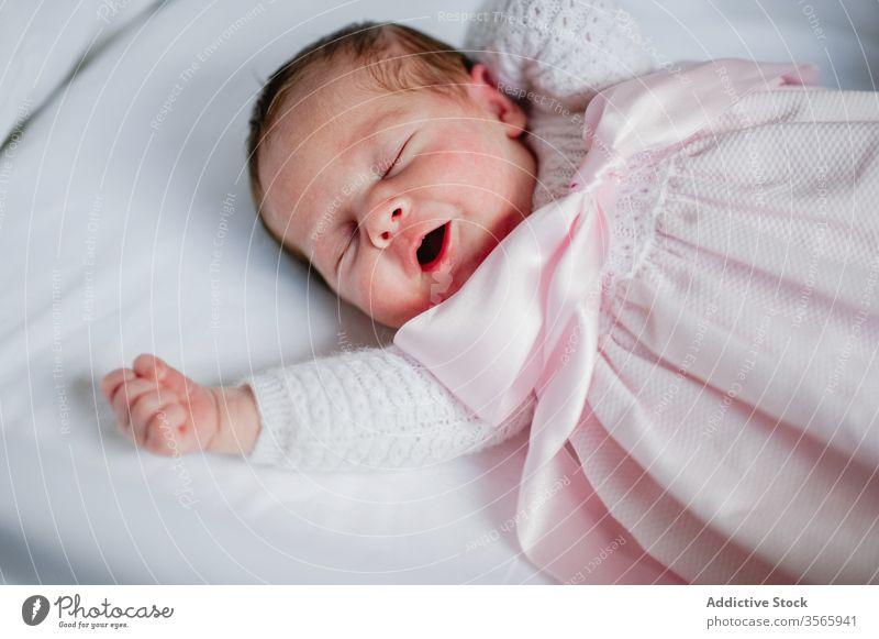 Neugeborenes Mädchen gähnt in Krippe neugeboren gähnen Baby Babybett Kinderbett bezaubernd Lügen schlafen niedlich gemütlich Kleid Säugling unschuldig ruhen