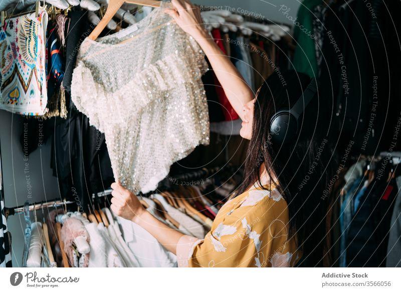 Junge attraktive Frau mit Kleidung in der Garderobe Kleiderschrank Kleidungsstück pflücken heimwärts Robe Bekleidung Stoff wählen Outfit Mode Stil brünett Wahl