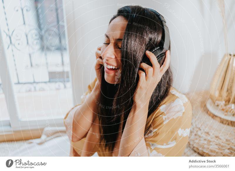 Glückliche Frau mit Kopfhörern, die zu Hause Musik hört Raum Gesang zuhören Kälte genießen Komfort räkeln Schlafzimmer sich[Akk] entspannen Lifestyle ruhen