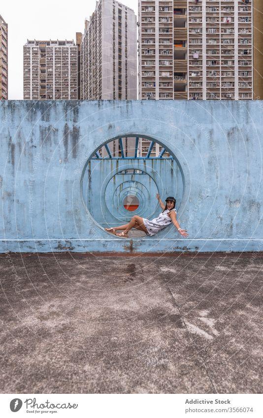 Frau sitzt an Mauern mit Tunnel in Hongkong Wand Stollen Durchgang Straße Installation Großstadt ungewöhnlich kreativ Sommer shek kip mei Hongkong Kong rund