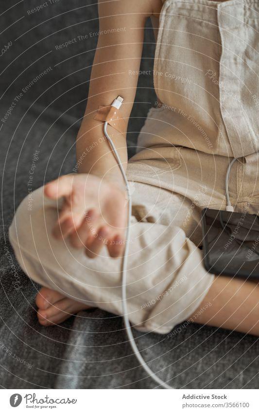 Kind mit Smartphone und USB-Kabel als Tropfenzähler beschneiden Junge abhängig Süchtige usb-kabel Apparatur Abwurfzähler Heftpflaster sitzen Handy Konzept