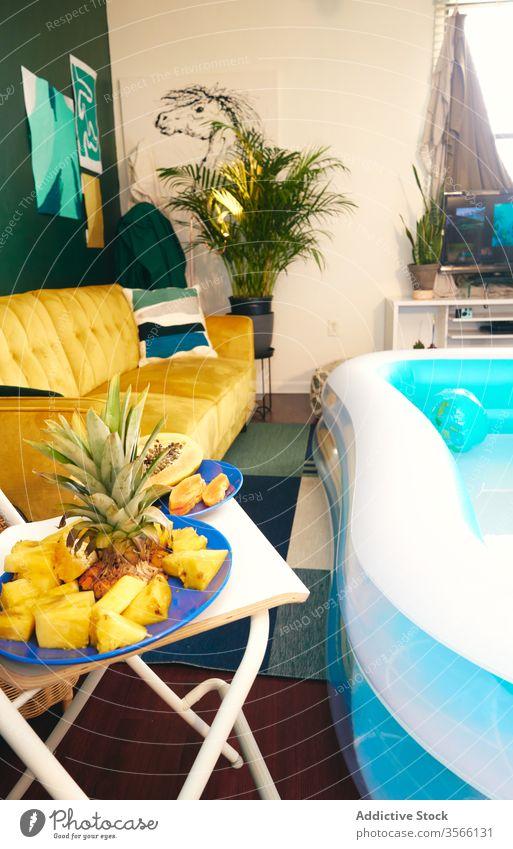 Innenraum des Wohnzimmers mit aufblasbarem Pool Party tropisch zu Hause bleiben Selbstisolierung Frucht Innenbereich soziale Distanzierung Appartement heimwärts
