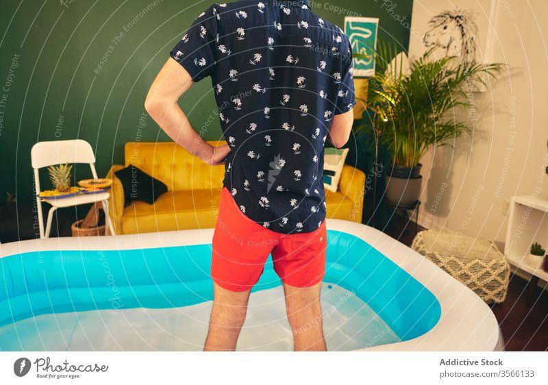 Mann im aufblasbaren Pool während Hausparty heimwärts Party zu Hause bleiben Sommer Appartement kreativ Selbstisolierung Spaß haben Wasser männlich Shorts Hemd