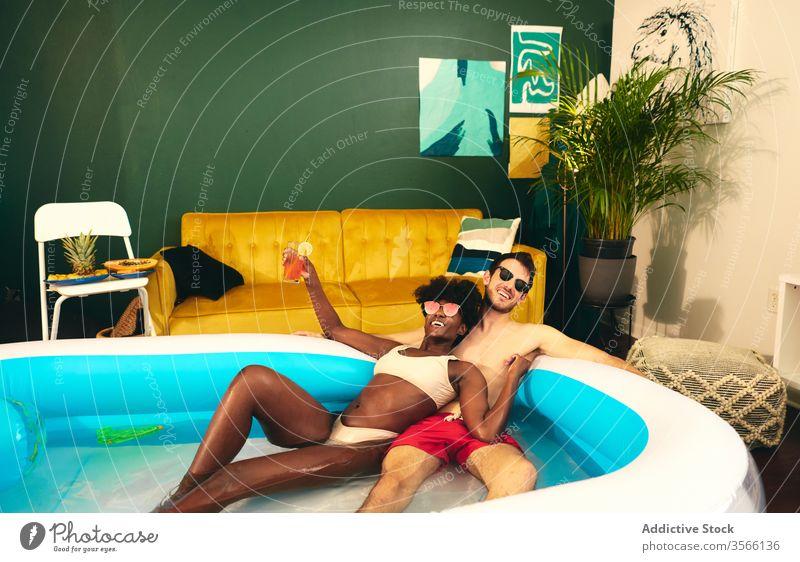 Inhalt multiethnisches Paar ruht sich im aufblasbaren Pool aus Party zu Hause bleiben Spaß haben Selbstisolierung verliebt soziale Distanzierung Wasser