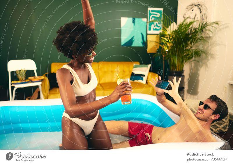 Zufriedenes multiethnisches Paar beim Fotografieren und Entspannen im Pool fotografieren sich[Akk] entspannen aufblasbar Party zu Hause bleiben Cocktail