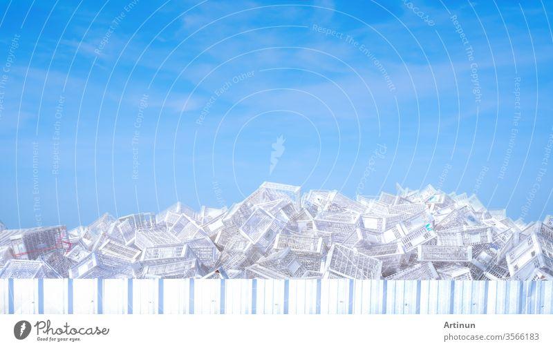 Ein Stapel weißer Plastikkörbe im Außenlager der Fabrik. Viele leere Plastikkörbe vor blauem Himmel und weißen Wolken. Korb für Ladenprodukte. Gestapelte Plastikkisten. Fracht und Versand.