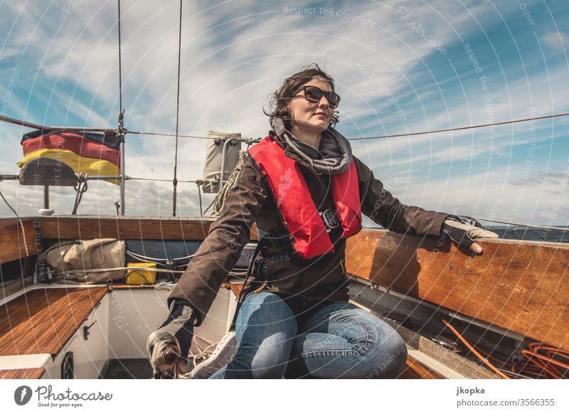 Junge Frau segelt auf der Ostsee Segeln Boot Yacht Jacht Segelboot Abenteuer Wasser Urlaub Schiff Nautisch Reisen Segelschiff Außenaufnahme Schiffsdeck Klassik