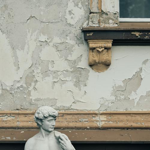 Kopf einer männlichen Statue vor Fassade mit abblätternder Farbe und Stuck-Detail eines Fensters römisch Rom braun grau alt Fensterrahmen Mauer Verfall