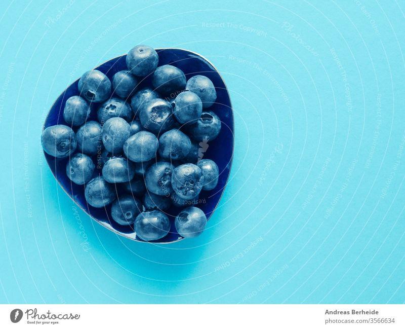 Schmackhafte Bio-Blaubeeren auf blauem Papierhintergrund organisch Antioxidantien Entzug Draufsicht nass Saft Gesundheit Vitamin Ernährung Diät Haufen