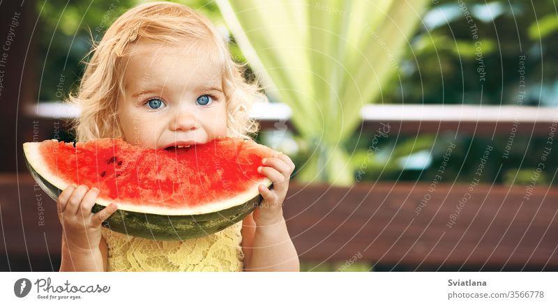 Kleines blondes Mädchen isst im Garten eine saftige Wassermelone. Kinder essen Obst auf der Straße. Gesundes Essen für Kinder. Kleinkind beim Gärtnern. Frucht