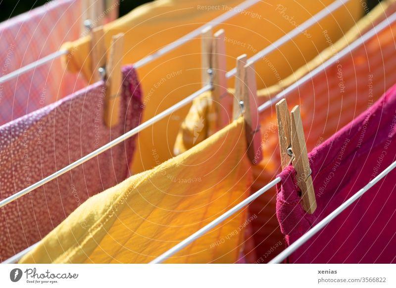 Sommerwäsche - Kleidung in gelb und rosa hängt auf dem Kleiderständer Wäsche Wäscheklammer trocknen Wäscheleine Waschtag Haushalt Bekleidung Sauberkeit