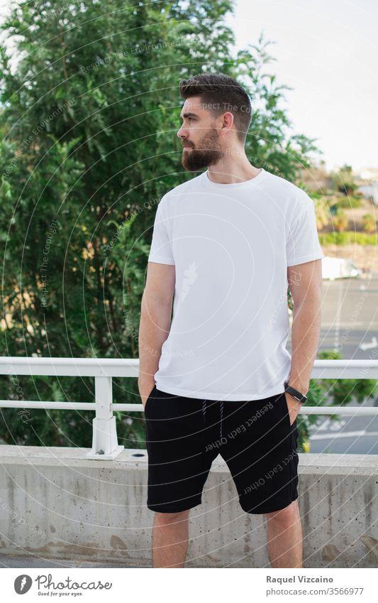 Lässiges Modell Mann im Freien, sehr gut aussehend, mit weißem T-Shirt und urbanem Stil Porträt jung gutaussehend Glück Hemd Lächeln Person Menschen Park lässig
