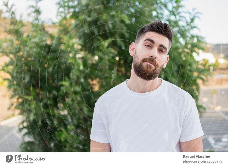 Hübscher Mann mit Bart und weißem T-Shirt im Freien. Porträt jung gutaussehend Glück Hemd Lächeln Person Menschen Park lässig Typ Gesicht Männer Vollbart