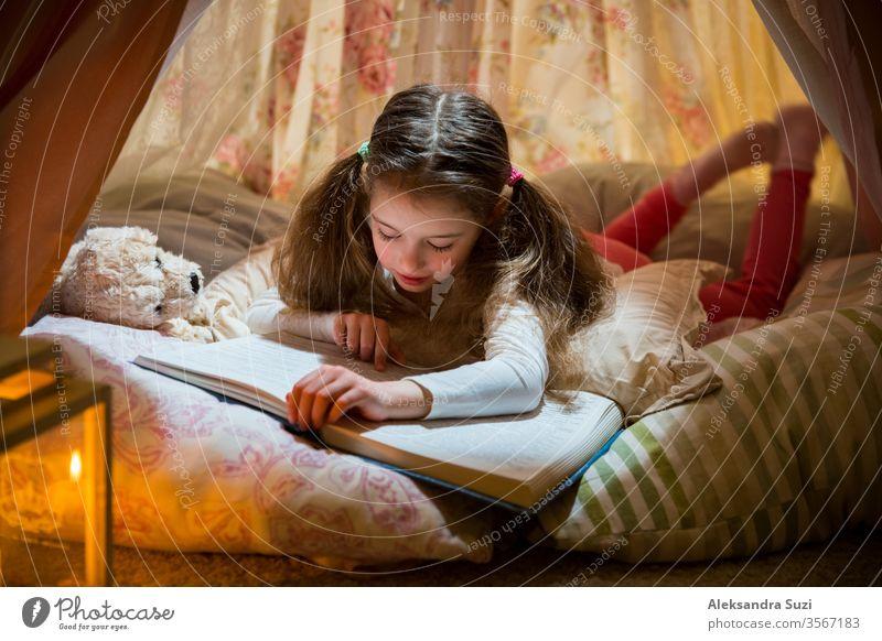 Süßes kleines Mädchen auf Kissen liegend in hausgemachtem rosa Zelt mit Blumen, großes Buch mit Interesse und Aufmerksamkeit lesen. Gemütliches stilvolles Zimmer.