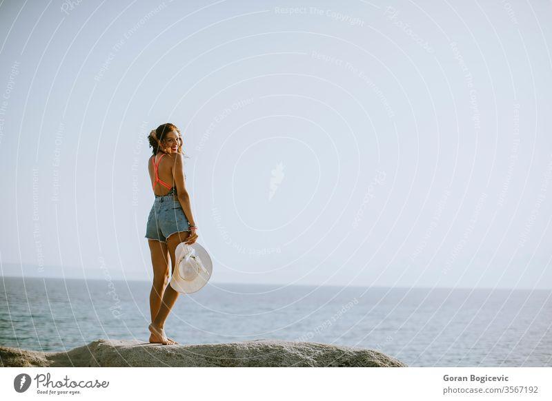 Junge Frau im Bikini auf Felsen am Meer stehend Erwachsener attraktiv Strand schön blau brünett Kaukasier Küste Tag Griechenland Behaarung Feiertag Freizeit