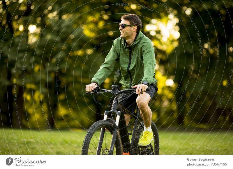 Junger Mann fährt E-Bike in der Natur Fahrrad Batterie Biker ebike Sport Berge u. Gebirge elektrisch Radfahren Sommer extrem Radfahrer grün im Freien reisen