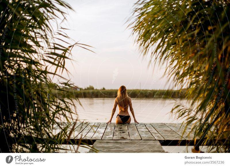 Junge Frau im Bikini auf einem Pier am See sitzend allein attraktiv Strand schön Schönheit blond sorgenfrei Kaukasier Model Natur im Freien Person posierend