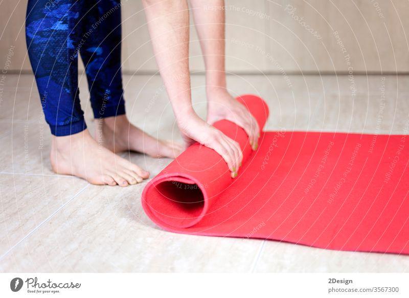Nahaufnahme eines jungen Mädchens, das die Yogamatte aufrollt Übung Unterlage Frau Fitness aktiv Körper schön Klasse Gerät Lifestyle Hintergrund Erholung