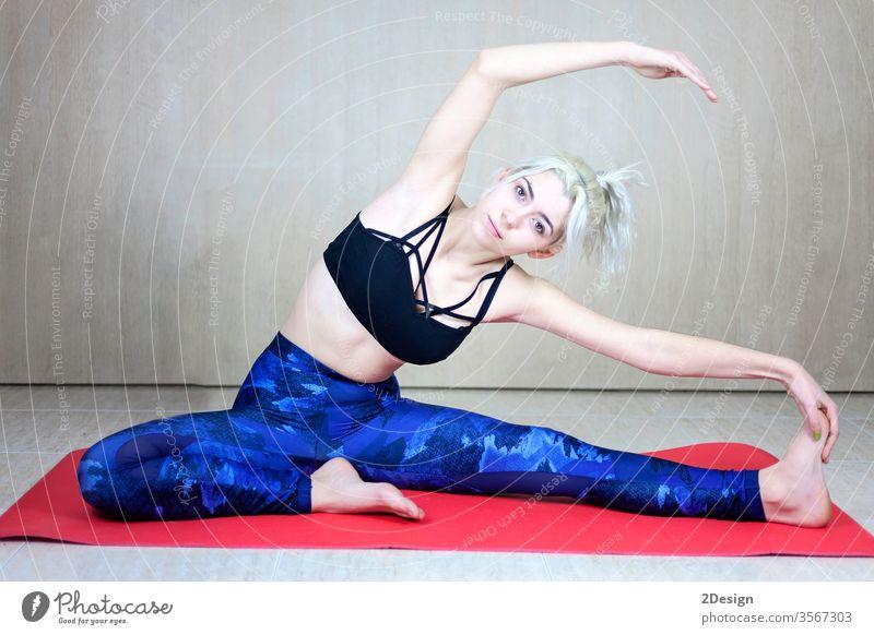 Frau macht Dehnübungen zum Aufwärmen im Haus über einer Yogamatte Person Übung Fitness Gesundheit Lifestyle schön Körper jung Sport Mädchen Schönheit Erholung