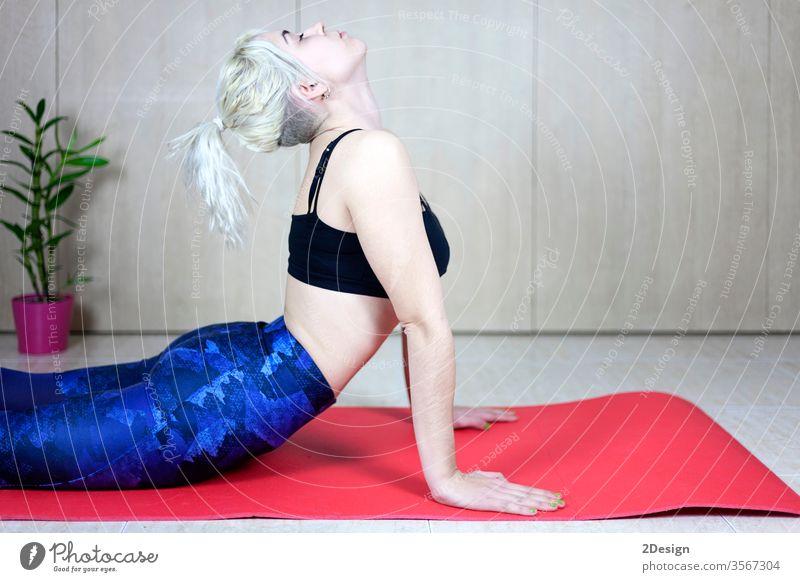 Junge sportliche Frau, die sich drinnen auf der Matte zurückstreckt Person strecken Rücken Sport Mädchen Lifestyle Fitness Training Yoga Körper Erwachsener