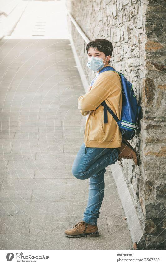 Kind mit medizinischer Maske und Rucksack wartet an der Schultür Coronavirus Virus Seuche covid-19 Schule Schüler Pandemie Quarantäne zurück zur Schule