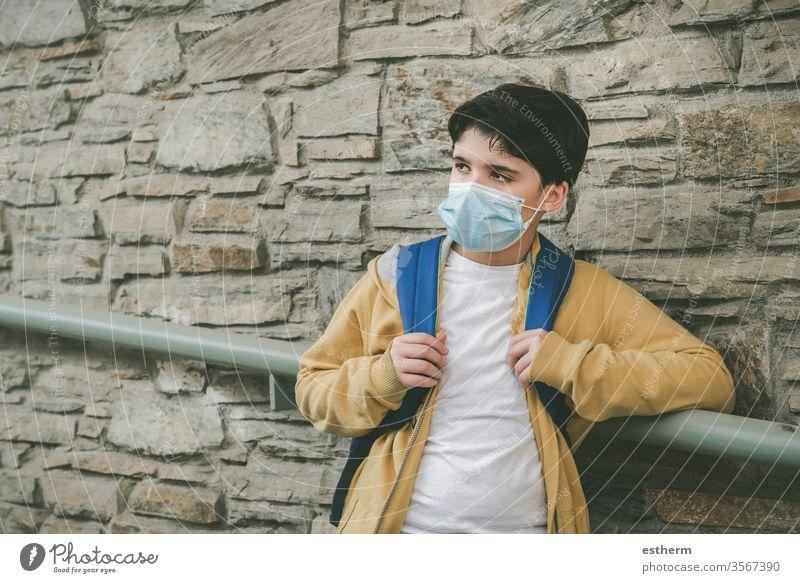 Kind mit medizinischer Maske und Rucksack wartet an der Schultür Coronavirus Virus Seuche covid-19 Schule schuler Pandemie Quarantäne zurück zur Schule
