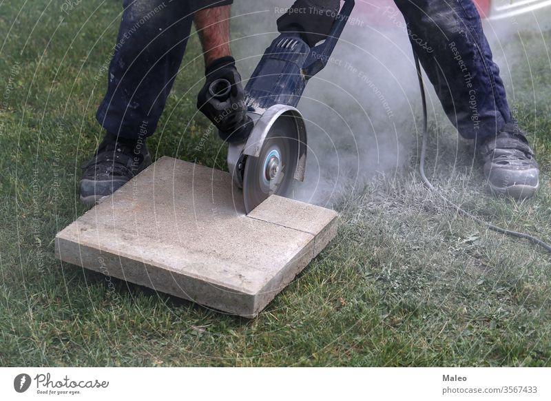 Industriebauarbeiter mit einem professionellen Winkelschleifer Baustein Schlacke kreisrund Nahaufnahme Kragen Beton Konstruktion kupfer Schnurlos Handwerk