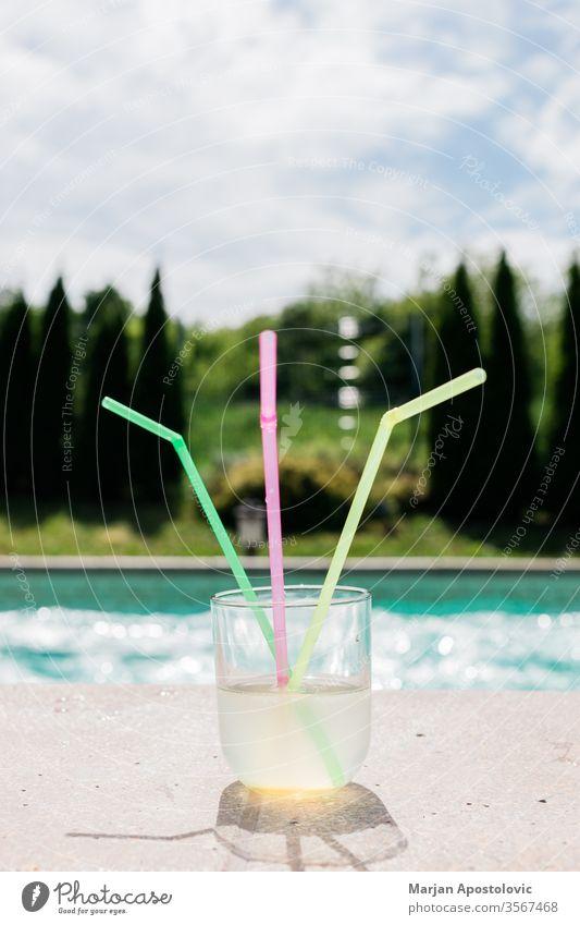 Glas Limonade mit drei Strohhalmen am Schwimmbad alkoholisch aqua Getränk blau Cocktail kalt farbenfroh Farben cool Kopie trinken genießen exotisch frisch