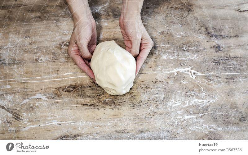 Hände kochen, die einen Pizzateig herstellen und mit Tomaten, Champignons, Schinken, Mozzarella und Parmesankäse zubereiten. Teigwaren Lebensmittel