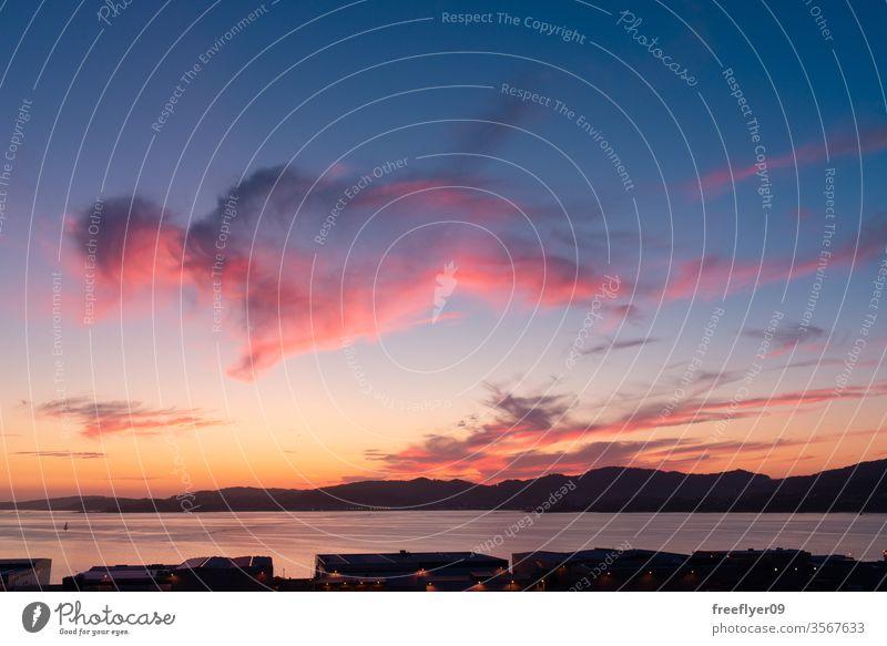 Wolkenreicher Himmel bei Sonnenuntergang mit warmen Tönen Morgendämmerung schön reisen Wasser Abenddämmerung Landschaft Natur Ansicht Strand Sonnenaufgang