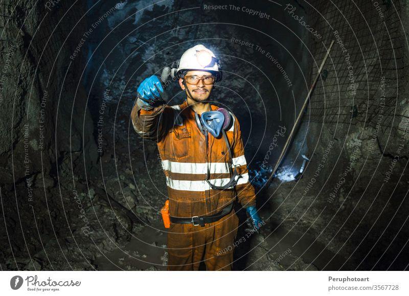 Bergmann in der Mine. Gut uniformierter Bergmann im Bergwerk, der den Daumen hebt Bergarbeiter Höhle industriell unterirdisch Schacht eine im Freien Outfit