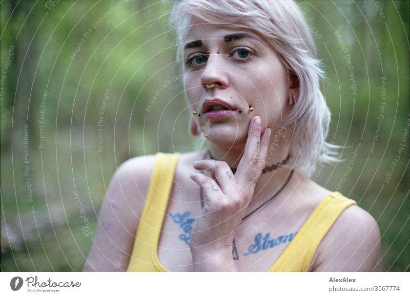 Analoges Portrait einer jungen Frau mit Piercings, Tätowierungen und Tunnel Mädchen blond Schmuck Assecoires Schulter Shirt Hemd schön draussen schauen