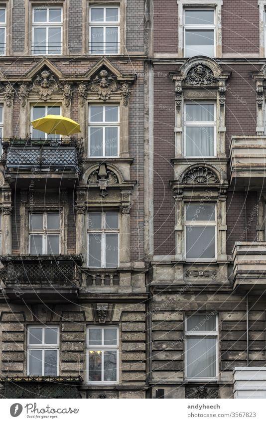 Gelber Sonnenschirm auf dem Balkon eines alten Gebäudes antik Appartement Appartements architektonisch Architektur Balkone Berlin Baustein Großstadt Stadtbild