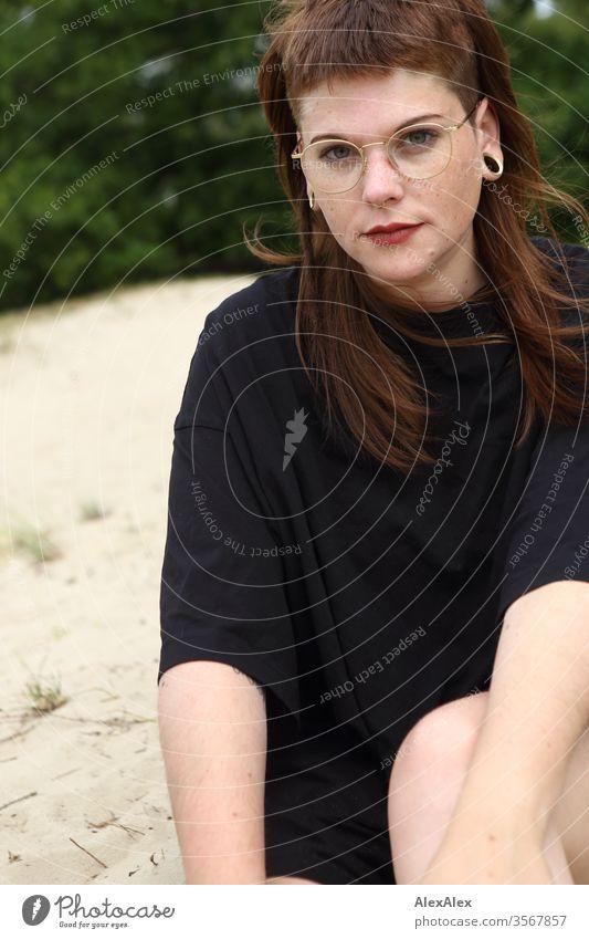 Portrait einer jungen Frau im Park Jugendliche schön stark alternativ groß Piercing Haut intensiv Blick schauen beaobachten stehen schlank ästhetisch sportlich