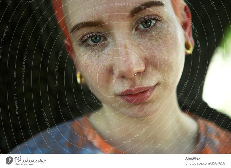 Portrait einer jungen Frau vor einem Baum 18-25 Jahre schön Schlank Sommersprossen rothaarig schmuck Piercing Tätowierung Gesicht hellhäutig kurzhaarig weiß