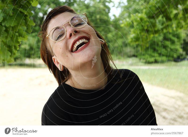 Portrait einer lachenden jungen Frau im Park Jugendliche schön stark alternativ groß Piercing Haut intensiv Blick schauen beaobachten stehen schlank ästhetisch