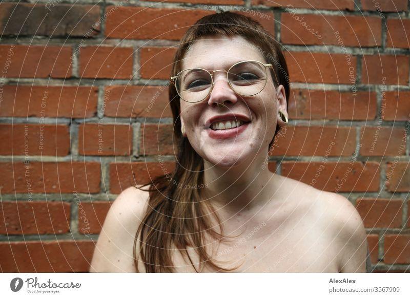 Portrait einer lachenden jungen Frau vor einer Backsteinwand Jugendliche schön stark alternativ groß Piercing Haut intensiv Blick schauen beaobachten stehen