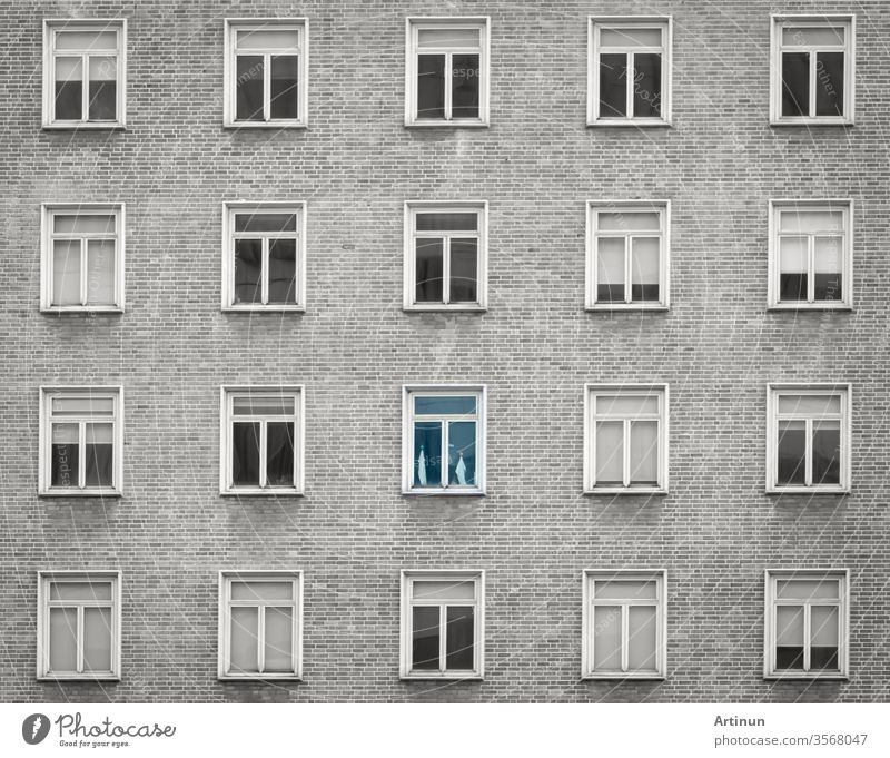 Glasfenster einer Wolkenkratzerwohnung oder eines Hotelgebäudes. Äußere Ziegelwand eines Wohngebäudes. Entwurf der Architektur. Fenster der Gebäudetextur Hintergrund. Grau-weißes Vintage-Gebäude.