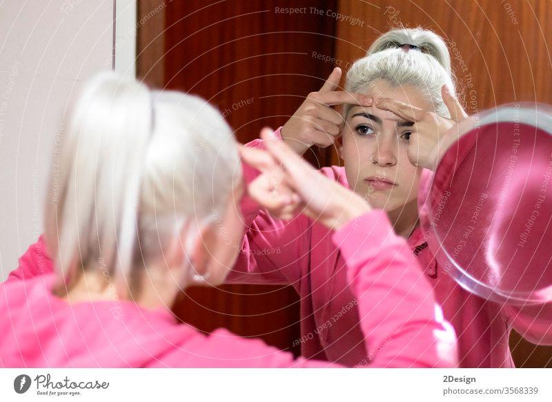 Frau im Bademantel, die einen Pickel im Gesicht in den Spiegel schaut und versucht, ihn zu drücken. Person Schönheit Akne Haut Pflege Erwachsener jung Blick