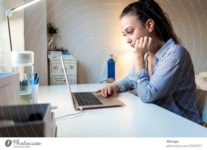 Seitenansicht einer jungen Frau, die zu Hause mit einem Laptop arbeitet Person Business Geschäftsfrau Computer Technik & Technologie Erwachsener studierend
