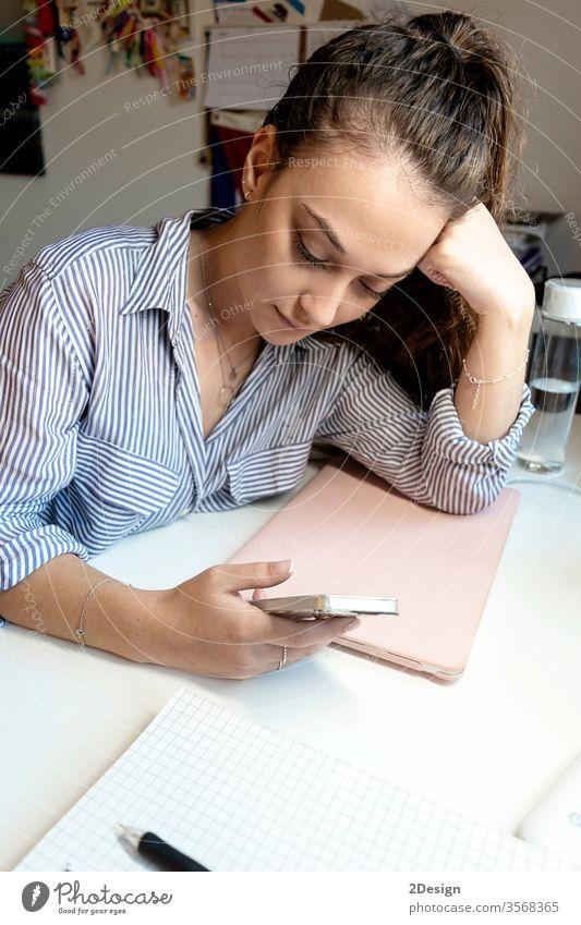 Junge Frau, die an einem Laptop sitzt und ein Smartphone benutzt. Computer Büro Business Person Schreibtisch Technik & Technologie Geschäftsfrau jung