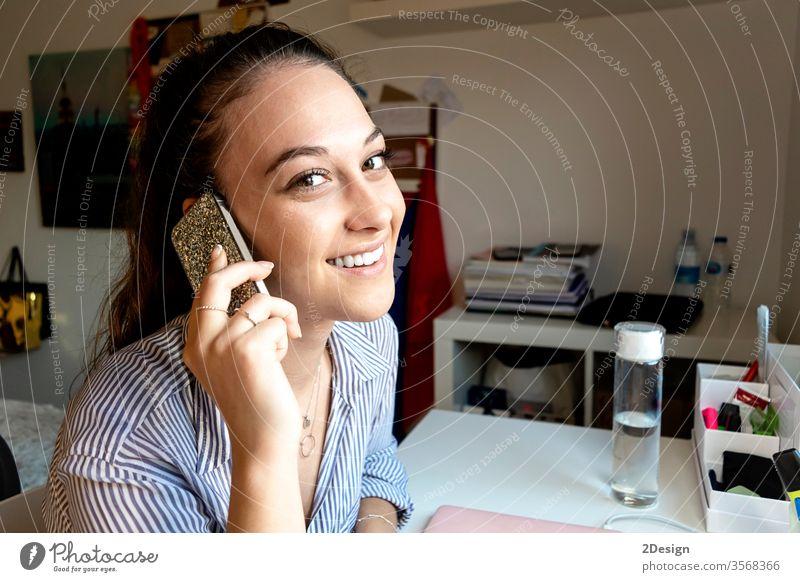 Lächelnde Frau mit einem Telefongespräch zu Hause Mitteilung Erwachsener Person Schreibtisch Handy Technik & Technologie Business im Innenbereich Sitzen