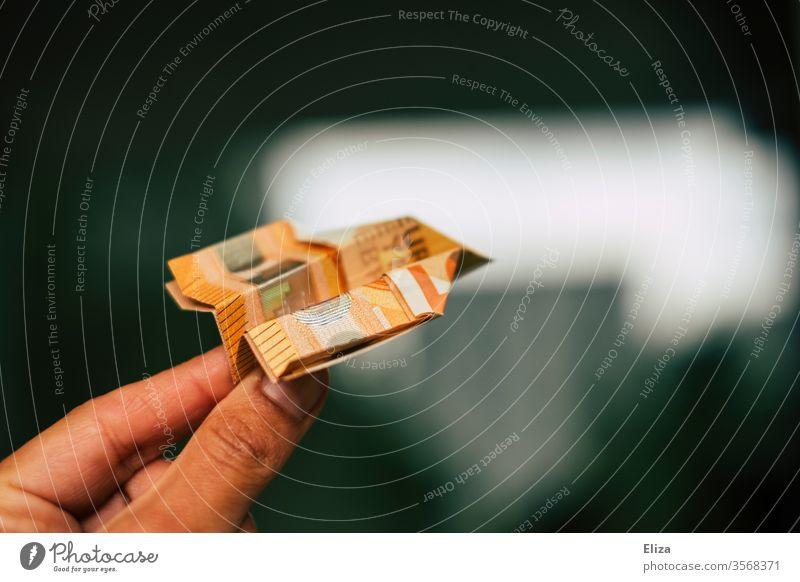 Eine Hand fliegt einen aus einem Geldschein gefalteten Papierflieger. Geldanlage, Investition. fliegen reisen Urlaub Kosten Urlaubskasse teuer Flugzeug Pass