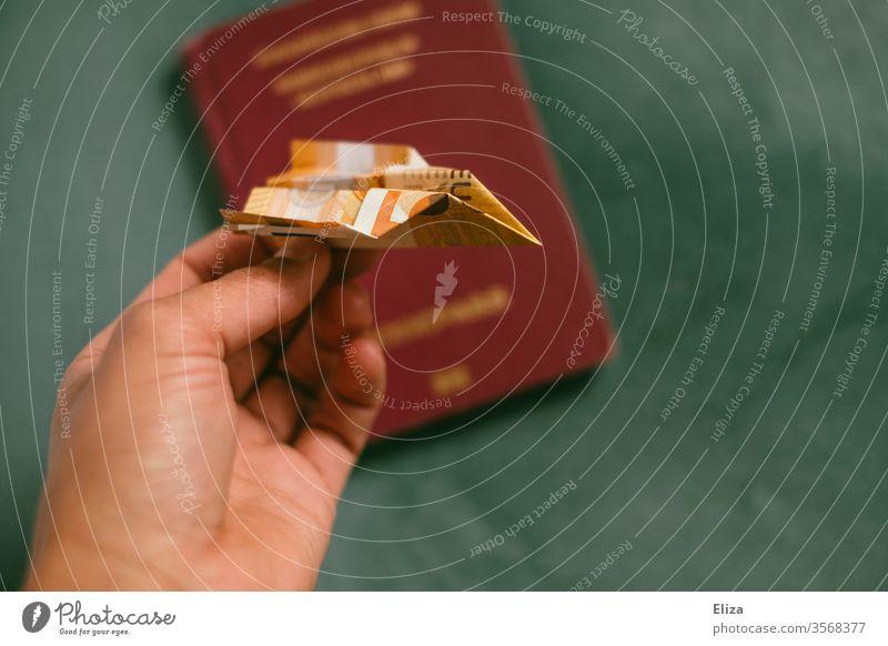 Eine Hand hält einen gefalteten Papierflieger aus einem Geldschein über einen Reisepass. Konzept Reisen, Urlaub und Fliegen. fliegen reisen Kosten Urlaubskasse