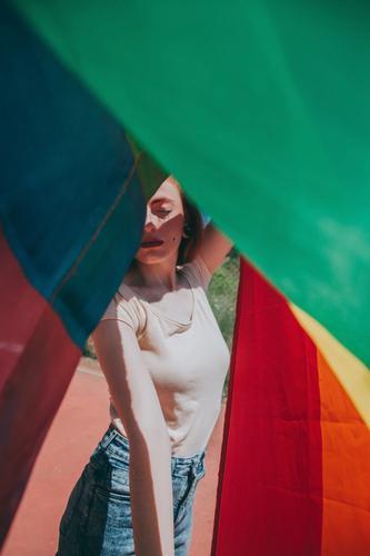 Junge Frau bedeckt von einer Regenbogenfahne lgbti schwul Stolz Party Fahne Homosexualität lesbisch Farbe farbenfroh im Freien sozial Problem Geschlecht