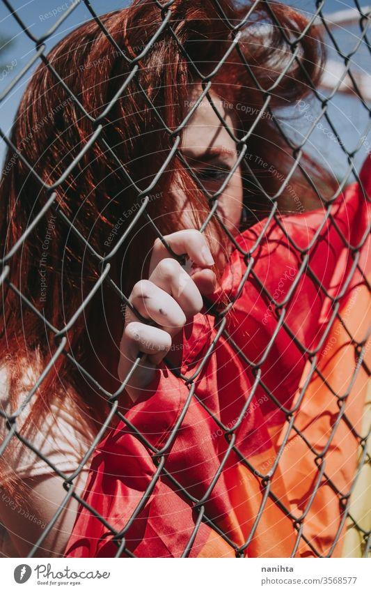 Junge traurige Frau bedeckt von einer Regenbogenfahne lgbti schwul Stolz verboten Fahne Homosexualität lesbisch Farbe farbenfroh im Freien sozial Problem