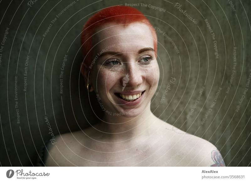 Portrait einer lachenden jungen Frau vor einer Betonwand 18-25 Jahre schön Schlank Sommersprossen Wand rothaarig schmuck Piercing Tätowierung Dekolleté Gesicht