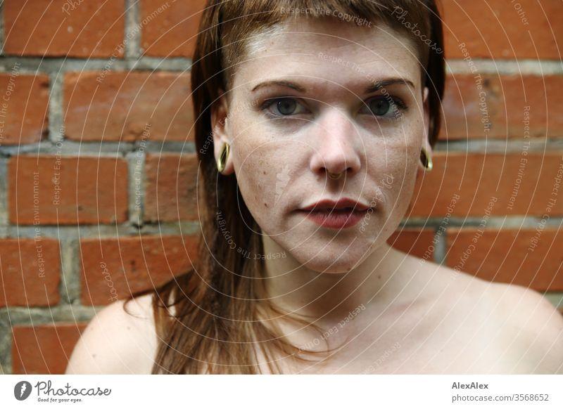 Portrait einer jungen Frau vor einer Backsteinwand Jugendliche schön stark alternativ groß Piercing Haut intensiv Blick schauen beaobachten stehen schlank
